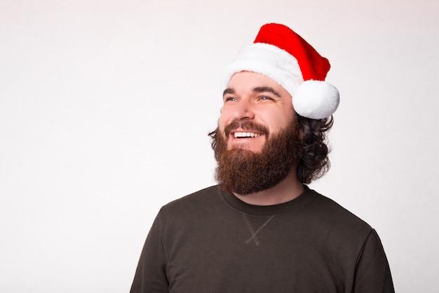 笑顔で目をそらしてサンタクロースの帽子をかぶったひげを生やした男の肖像画 Premium写真