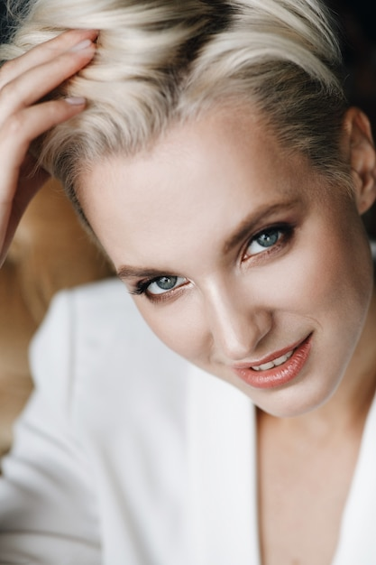 Portrait Of Beauitful Blonde Woman With Short Hair And Deep Blue