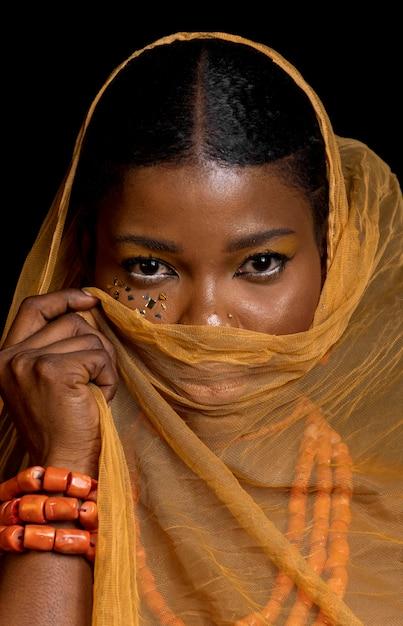 伝統的なアクセサリーと黄色のベールを身に着けている美しいアフリカの女性の肖像画 無料写真