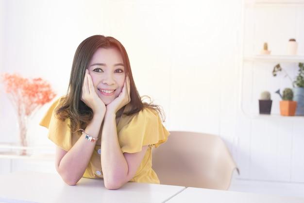 Портрет красивой азиатской женщины отдыхает ее голень на ее руках с стороной улыбки и смотрит вне окно с космосом экземпляра. Premium Фотографии