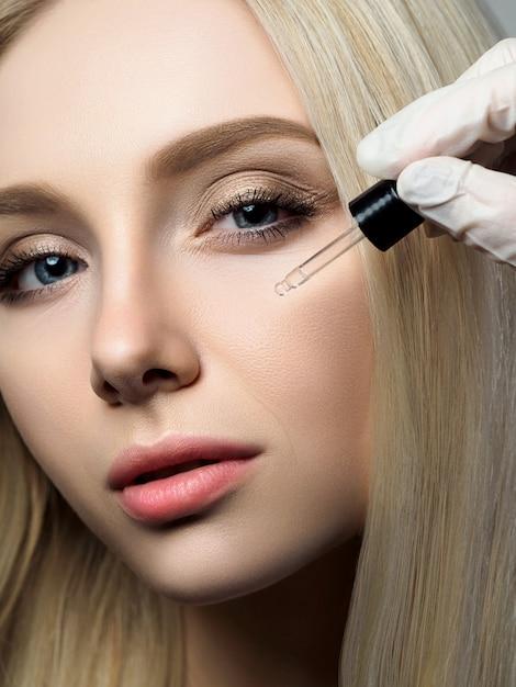 Портрет красивой белокурой женщины в салоне красоты. косметолог, применяя капли красоты Premium Фотографии