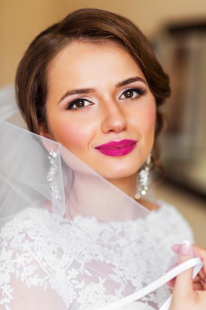 明るい白いウェディングドレスで美しい花嫁の肖像画を占めています。新婚女性の結婚式のための最終的な準備。 無料写真