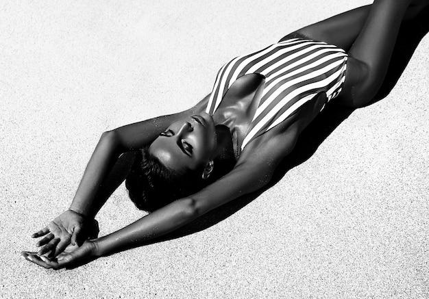 Портрет красивой кавказской загорелой женщины модель с темными длинными волосами в полосатом купальнике позирует на пляже летом с белым песком Бесплатные Фотографии