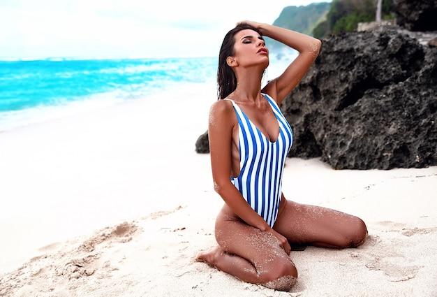白い砂浜と夏のビーチでポーズストライプ水着で黒い長い髪と美しい白人日光浴女性モデルの肖像 無料写真