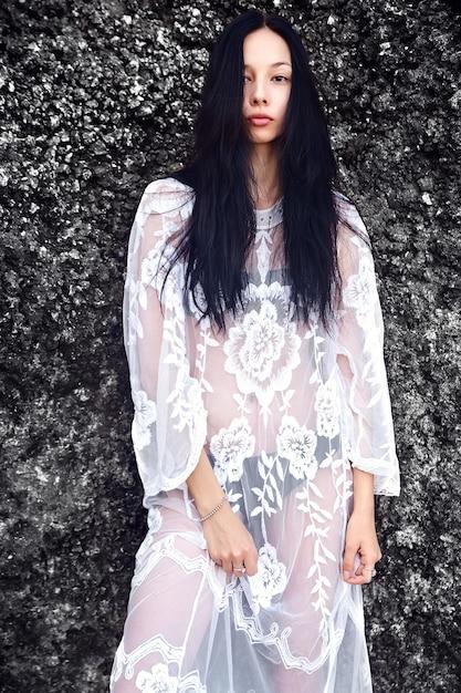 Портрет красивой кавказской модели женщины с темными длинными волосами в прозрачном белом длинном платье блузки, позирующем около скал Бесплатные Фотографии