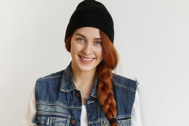 Портрет красивой веселой рыжей девушки в стильной черной зимней шапке и джинсовой куртке без рукавов Бесплатные Фотографии