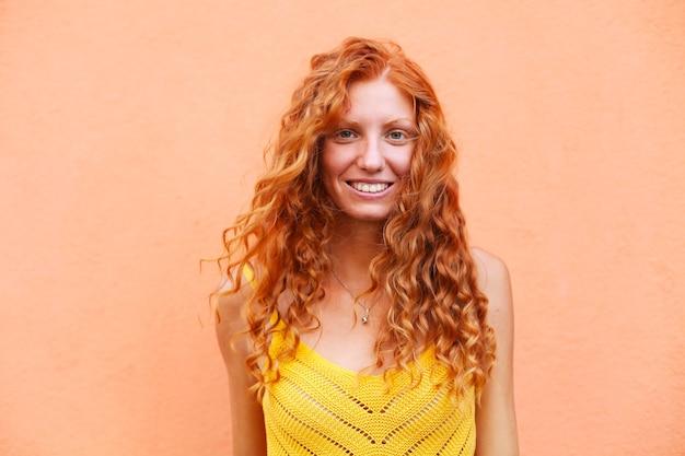 笑みを浮かべて巻き毛を飛んで美しい陽気な赤毛の女の子の肖像画 Premium写真