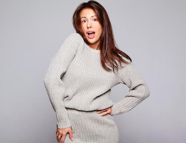 Портрет красивой милой брюнетки модели в повседневной осенней серой одежде свитера без макияжа, изолированной на сером Бесплатные Фотографии