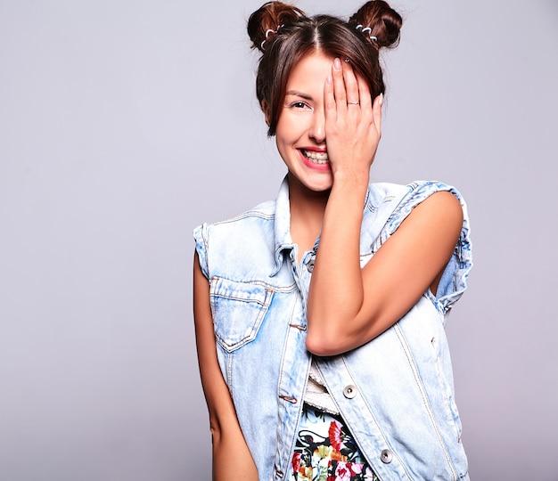 Портрет красивой милой модели женщины брюнет в вскользь джинсах лета одевает без состава при стиль причёсок рожков изолированный на сером цвете. закрыв лицо рукой Бесплатные Фотографии