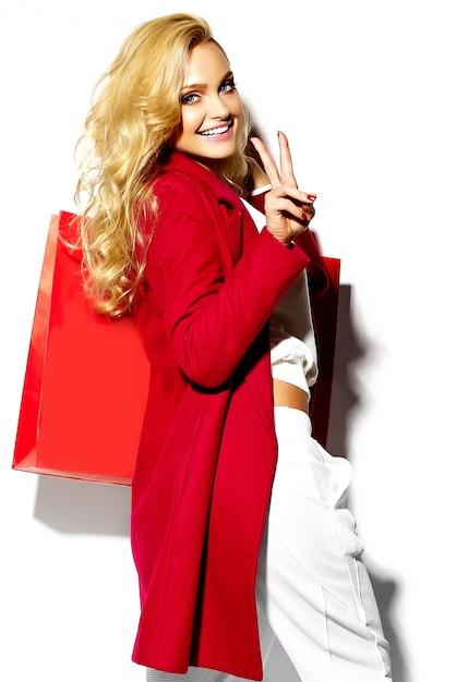 그녀의 손에 들고 아름 다운 귀여운 행복 달콤한 웃는 금발 여자 여자의 초상화는 흰색에 고립 된 소식통 빨간 옷에 큰 쇼핑백 무료 사진