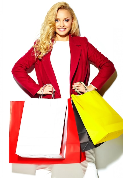 그녀의 손에 들고 아름 다운 귀여운 행복 달콤한 웃는 금발 여자 여자의 초상화 빨간 자 켓 Hipster에 큰 쇼핑 다채로운 가방에 격리 된 화이트 무료 사진