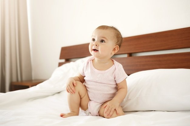 Портрет красивого милого славного newborn младенца в розовой рубашке сидя на кровати дома. Бесплатные Фотографии