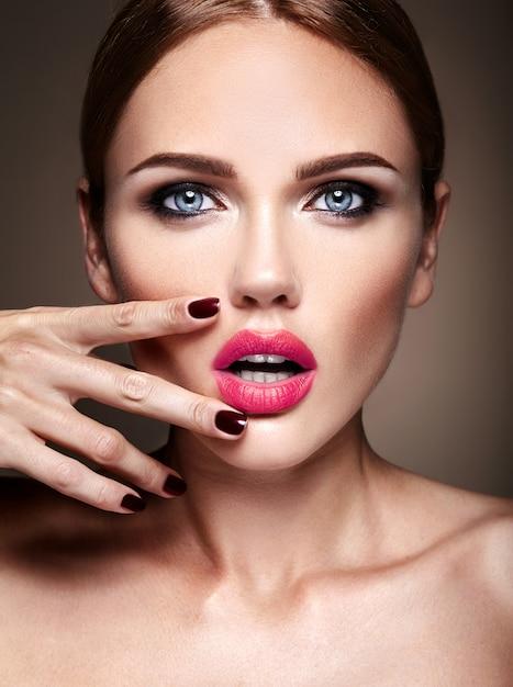 Портрет красивой девушки модели с вечернего макияжа и романтической прически. касаясь ее красных губ Бесплатные Фотографии