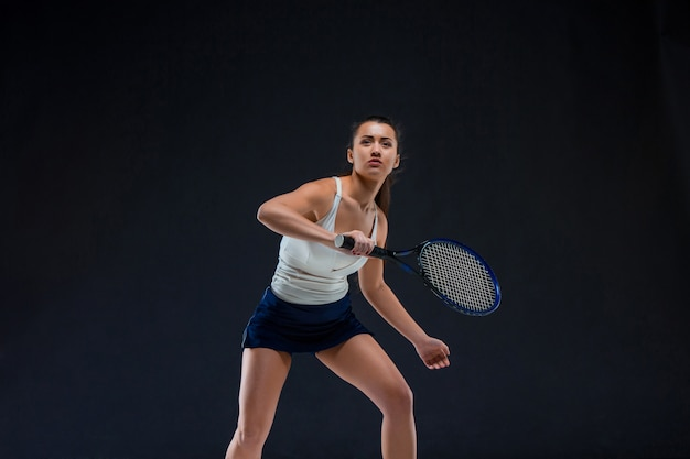 Портрет красивой теннисистки с ракеткой на темной стене Бесплатные Фотографии