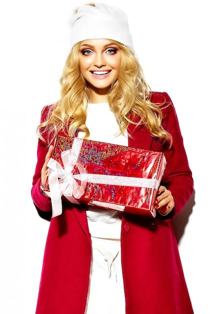 캐주얼 빨간 Hipster 겨울 옷에 그녀의 손에 큰 크리스마스 선물 상자를 들고 아름 다운 행복 달콤한 웃는 금발 여자 여자의 초상화 무료 사진