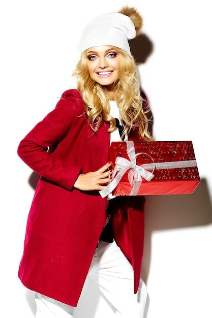 カジュアルな赤いヒップスター冬服で大きなクリスマスギフトボックスを手に持って美しい幸せな甘い笑顔金髪女性少女の肖像画 無料写真