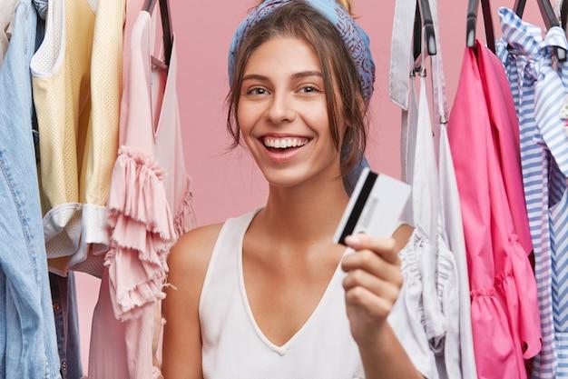 プラスチック製のクレジットカードを示し、元気に笑顔、買い物や新しい購入に興奮して服の中で店に立っている美しい幸せな若い白人女性の肖像画 無料写真