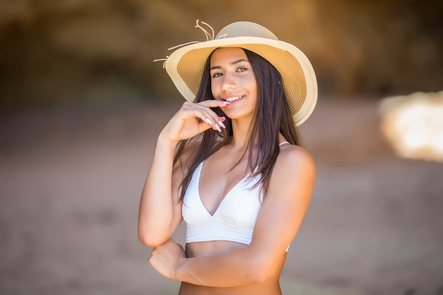 Портрет красивой латинской девушки на пляже с улыбкой в черной шляпе, аккуратным океаном и скалами на летних каникулах Бесплатные Фотографии