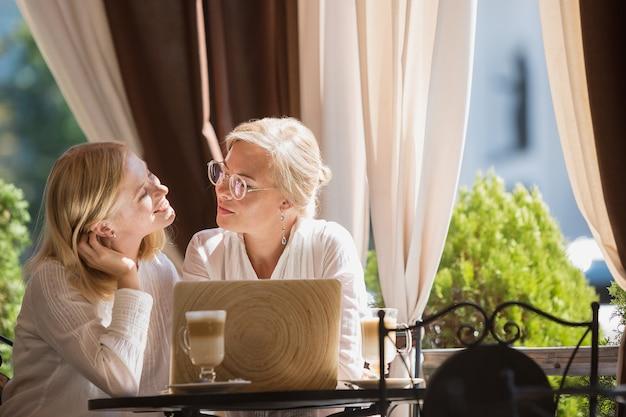 美しい成熟した母親と家に座ってカップを保持している彼女の娘の肖像画 無料写真