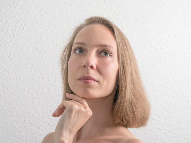 白い壁に彼女の顔に触れる美しい中年の女性の肖像画 Premium写真