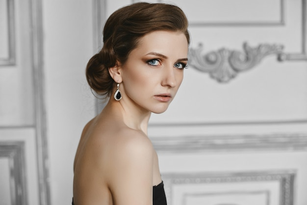 최신 유행 헤어 스타일 및 저녁 전문 메이크업으로 아름 다운 모델 여자의 초상화. 부드러운 입술과 연기가 자욱한 눈 고급 인테리어에 포즈 유행 여자의 모습. 프리미엄 사진