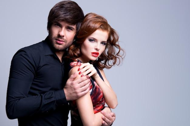 Портрет красивой страстной влюбленной пары на сером фоне Бесплатные Фотографии
