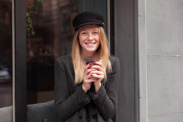 上げられた手でコーヒーのカップを保持し、灰色のエレガントな服を着て屋外でポーズをとって、魅力的な笑顔で元気に見える黒い帽子の美しいポジティブな若いブロンドの女性の肖像画 無料写真