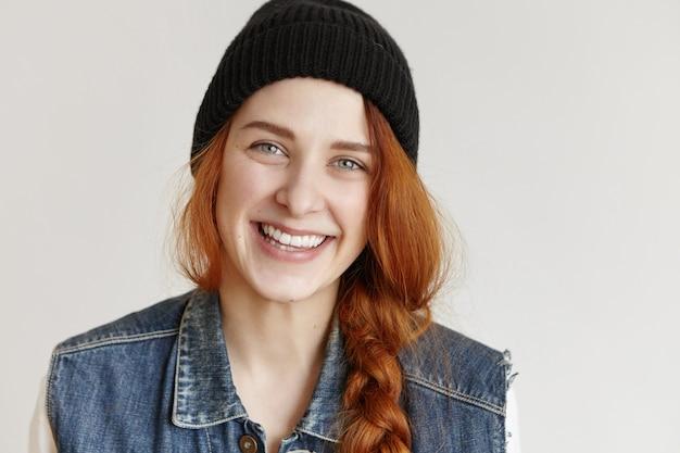 Портрет красивой рыжей молодой женщины в стильной черной шляпе и джинсовой куртке без рукавов Бесплатные Фотографии