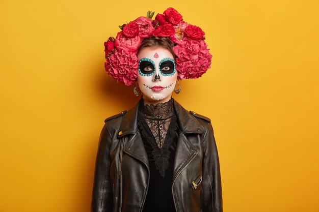아름다운 진지한 여자의 초상화는 창조적 인 생생한 화장을하고, 꽃 화환을 입고, 검은 옷을 입고, 무섭게 시도하고, 할로윈 휴가 파티 또는 죽음의 날에 온다 무료 사진