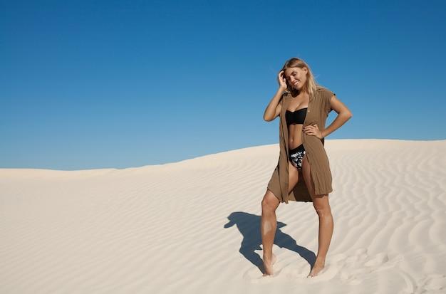 햇빛 야외에서 모래 바닥에 아름다운 섹시한 젊은 아가씨의 초상 프리미엄 사진