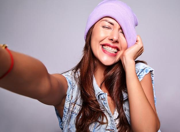 Портрет красивой улыбающейся милой брюнетки модели в повседневной джинсовой одежде без макияжа в фиолетовой шапочке, делающей селфи фото на телефон изолированную на сером Бесплатные Фотографии