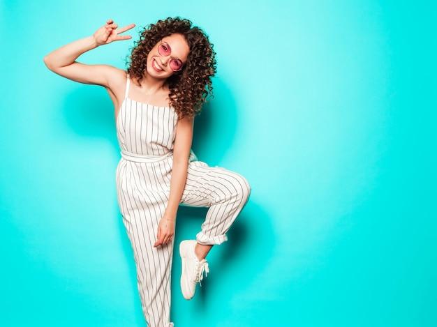 Портрет красивые улыбающиеся модели с афро кудри прическа, одетая в летней одежде битник. сексуальная беззаботная девушка позирует возле синей стены. модная смешная и позитивная женщина Бесплатные Фотографии