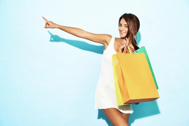 カラフルな紙袋を保持している美しい笑顔中毒者女性の肖像画。ショッピングの後の青い壁でポーズブルネットの女性。店頭販売に好意的なモデル 無料写真