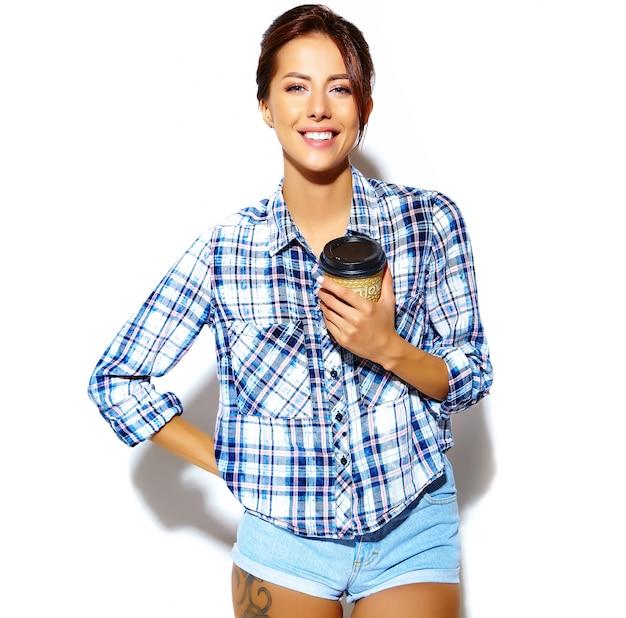 プラスチック製のコーヒーカップを保持している格子縞のシャツに夢中になる美しいスタイリッシュなクールな面白い10代女性の肖像画 無料写真
