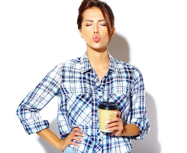 プラスチック製のコーヒーカップを押しながらキスを与える市松模様のシャツで美しいスタイリッシュなクールな10代女性の肖像画 無料写真