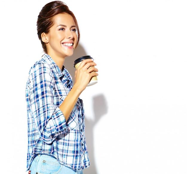 利用可能なプラスチックコーヒーcup.copyスペースを保持している市松模様のシャツで美しいスタイリッシュなクールな10代の女性の肖像画。 無料写真