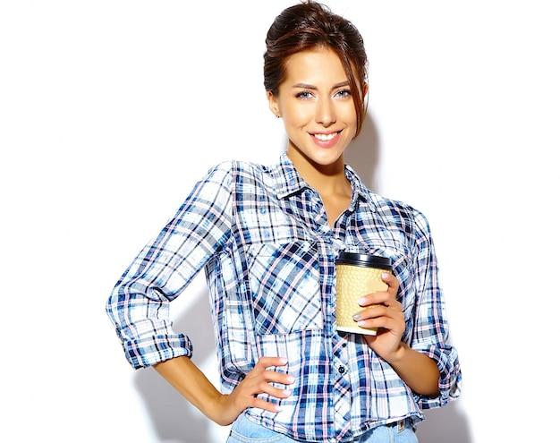 プラスチック製のコーヒーカップを保持している市松模様のシャツで美しいスタイリッシュなクールな10代女性の肖像画 無料写真