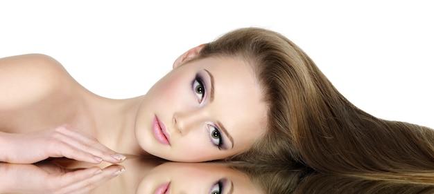 Портрет красивой девушки-подростка с длинными прямыми волосами, изолированной на белом Бесплатные Фотографии