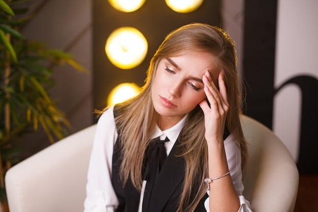 美しい疲れている学生の女の子の肖像画。オフィスに座っています。 Premium写真