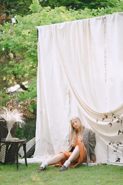 庭で、地面に座って、昼間はオレンジ色のドレスとジャケットを見て美しい女性の肖像画。 無料写真
