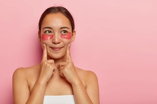 Портрет красивой женщины имеет свежую кожу, указывает на щеки, имеет гидрогелевые пятна под глазами, применяет коллагеновую маску против морщин, стоит, завернутый в полотенце, смотрит в сторону, изолированный на розовой стене. красота Бесплатные Фотографии