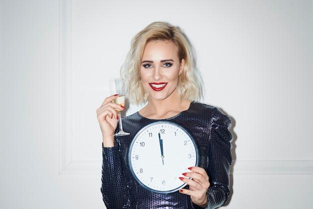 シャンパンと時計を保持している美しい女性の肖像画 無料写真