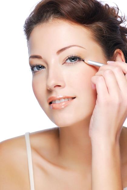 Портрет красивой женщины, делающей макияж с помощью черного косметического карандаша Бесплатные Фотографии