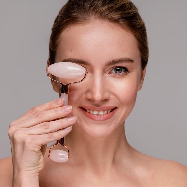 Портрет красивой женщины, использующей нефритовый ролик Бесплатные Фотографии