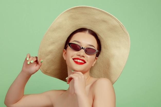 緑のスタジオの背景に明るいメイク、帽子、サングラスの美しい女性の肖像画。スタイリッシュでファッショナブルなメイクとヘアスタイル。夏の色。美容、ファッション、広告のコンセプト。笑顔。 無料写真