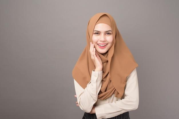 ヒジャーブと美しい女性のポートレートは灰色の壁に笑みを浮かべてください。 Premium写真