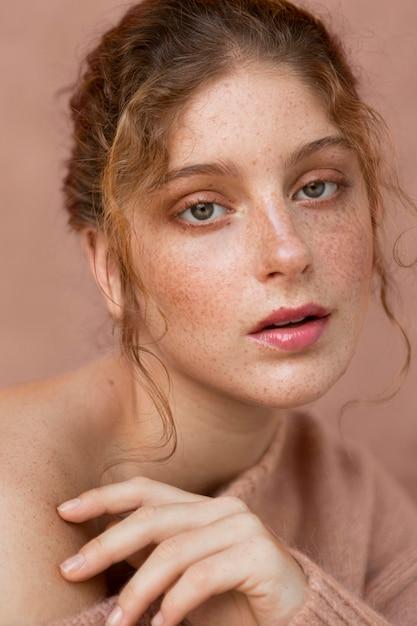 ピンクのセーターと裸の肩を持つ美しい女性の肖像画 無料写真