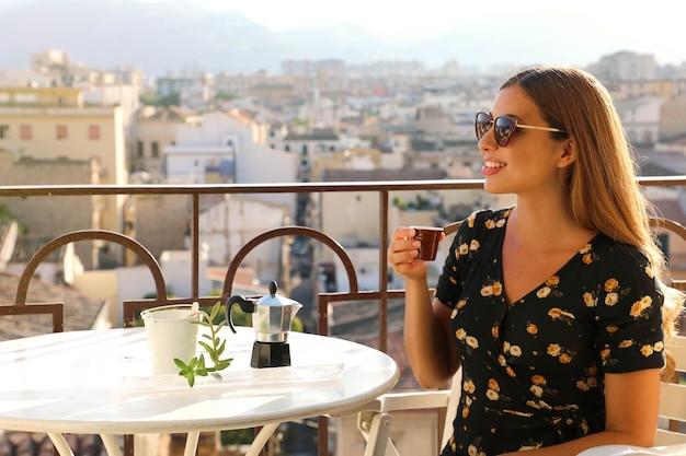 夕暮れ時にイタリアンコーヒーを飲むテラスに座っているサングラスと美しい女性のポートレート Premium写真