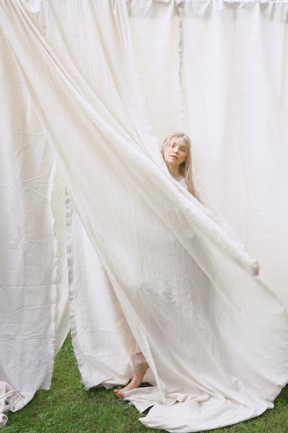 庭で立っていると昼間に白いドレスの布を保持している美しい女性の肖像画。 無料写真