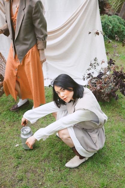 庭に立って、昼間に座っている美しい女性の肖像画。 無料写真